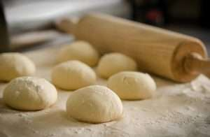 Pizza dough with flour beside a rolling pin