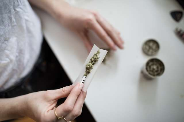 woman-placing-weed-and-dried-shrooms-in-a-paper-roll