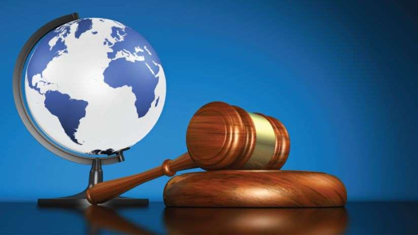 A gavel and base with a the earth globe in the background