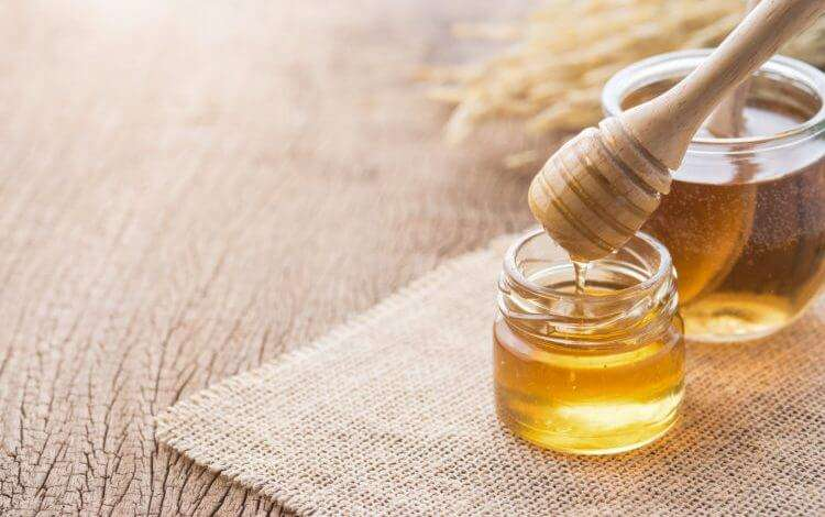 Honey dipping with a wooden honey dipper on a wooden table