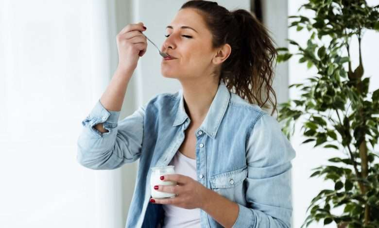 young woman eating yoghurt with a spoon and a plant background