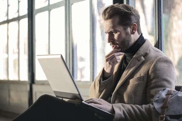 man thinking while looking at his laptop