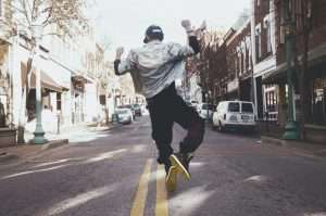 man-in-denim-jumping-happily-on-a-street