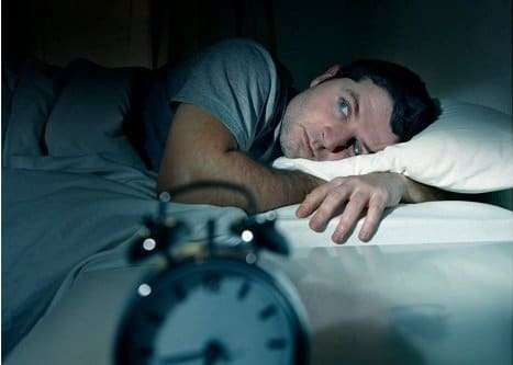 Man in bed with eyes opened with a clock infront