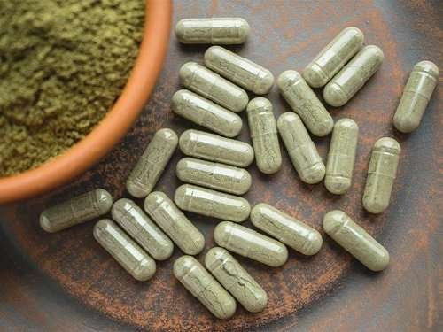 kratom in a green capsule with powder on the side