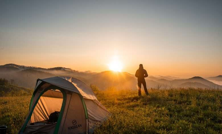 silhouette of person-standing near camping tent viewing the sunrise