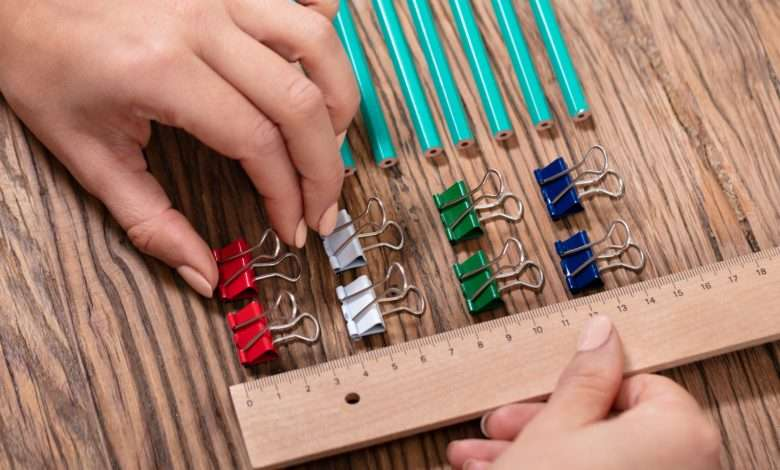 person arranging colorful paper clips with a wooden ruler
