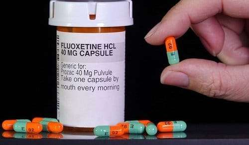 Prozac fluoxetine pill container with a hand showing 1 of the pill