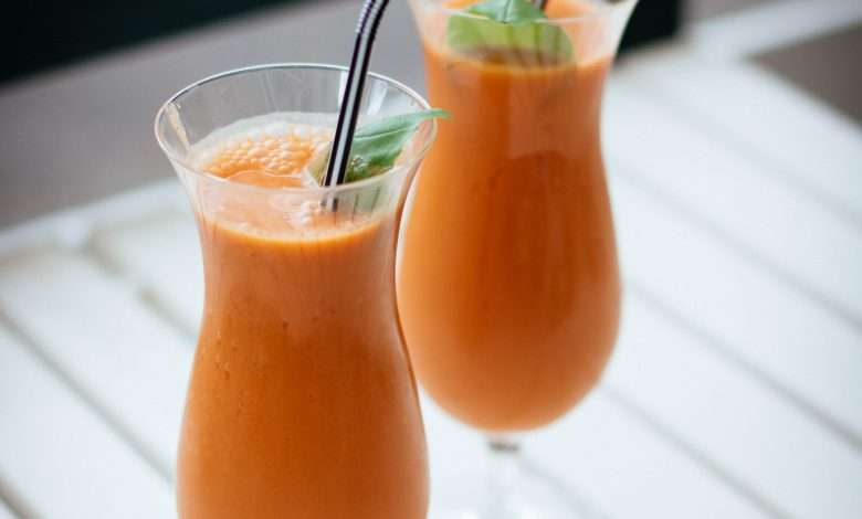 2 fruit juice in a glass with straw in the table