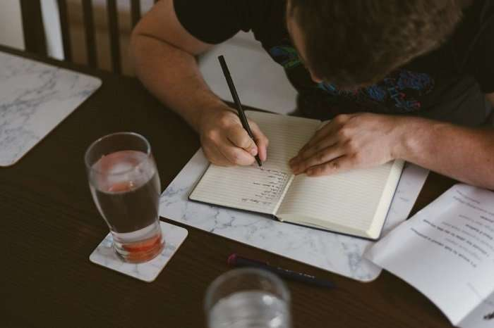 A man writing on a notebook